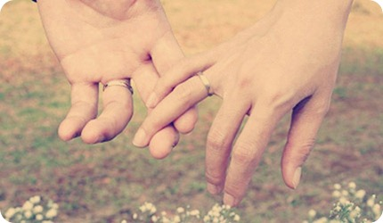 Couple holding hands with wedding bands on them