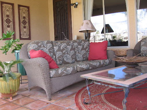 With the exception of the couch and chairs, everything on Lynda's porch comes from a garage sale. The lovely iron wall hangings above the couch were $4 total.