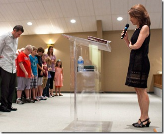 Bachmann prays, pic by Brendan Hoffman
