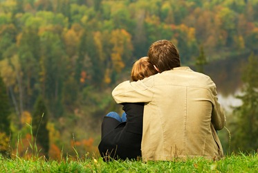 bigstock-Sweet-couple-sitting-on-a-hill-13194563