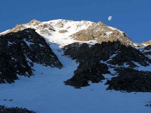 The moon is dwarfed by the north face of Sayres.
