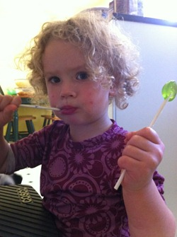 Young girl enjoying Black Pepper Melon lollipops