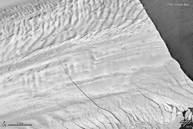 Aerial view of a crack in Pine Island Glacier, 31 October 2011. The massive rift runs about 29 kilometers (18 miles) across a part of the glacier's floating tongue. The rift is 80 meters (260 feet) wide on average, and 50 to 60 meters (170 to 200 feet) deep. NASA Earth Observatory image by Robert Simmon with data from the German Aerospace Center