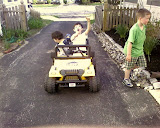 Kai and Eidan riding on the neighbor's battery powered mini Jeep