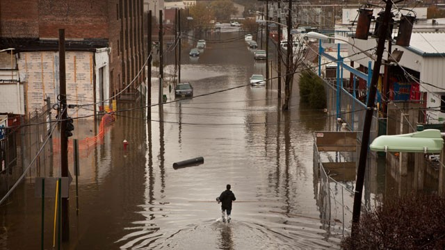 A man walks through flooded streets in Hoboken, New Jersey, after Hurricane Sandy. Photo: Emile Wamsteker / Bloomberg via Getty Images