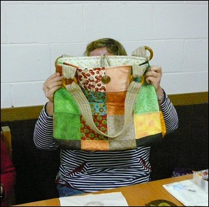 Margaret shows off her raffle win, a charm square bag.