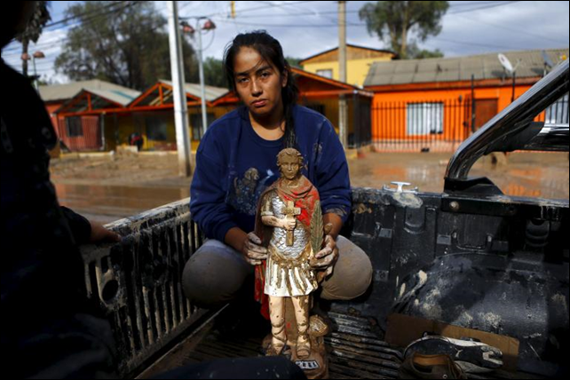 A woman holds a religious figure covered in mud as she is evacuated from her house at Copiapo city, 26 March 2015. The death toll in Chile rose after rains battered the north and caused flooding, the government said on Thursday, while 22 others were unaccounted for as the military rescued stranded villagers. Photo: Ivan Alvarado / REUTERS