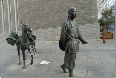 a statue of man going into town with his two donkeys