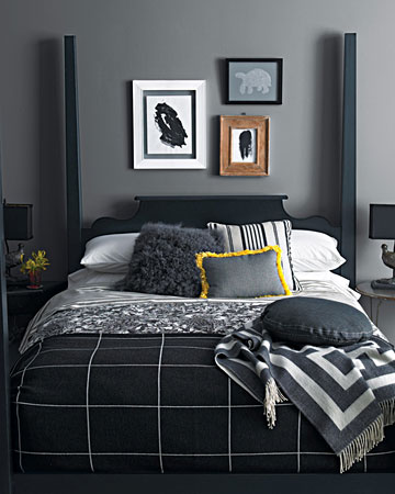 Layer on blacks and grays. We've mixed plaid and floral prints -- and shaggy pillows and plush throws -- on this black four-poster. Dark artwork and lamps carry the color scheme throughout the room, while a single shot of color -- the yellow-trimmed pillow -- keeps it lively.