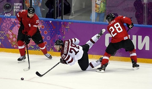 Feb 18, 2014; Sochi, RUSSIA; Latvia forward Zemgus Girgensons (28) loses his balance as he reaches for the puck between Switzerland forward Martin Pluss (28) and forward Nino Niederreiter (22) in a men's ice hockey playoffs qualifications game during the Sochi 2014 Olympic Winter Games at Bolshoy Ice Dome. Mandatory Credit: Winslow Townson-USA TODAY Sports