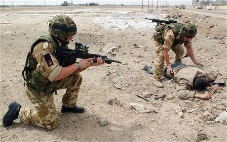 Britain's 2 Company Irish Guards check a man dressed in civilian clothes in Basra on 6 April 2003. Photo: Getty Images