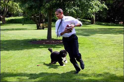 President Barack Obama runs away from the family dog
