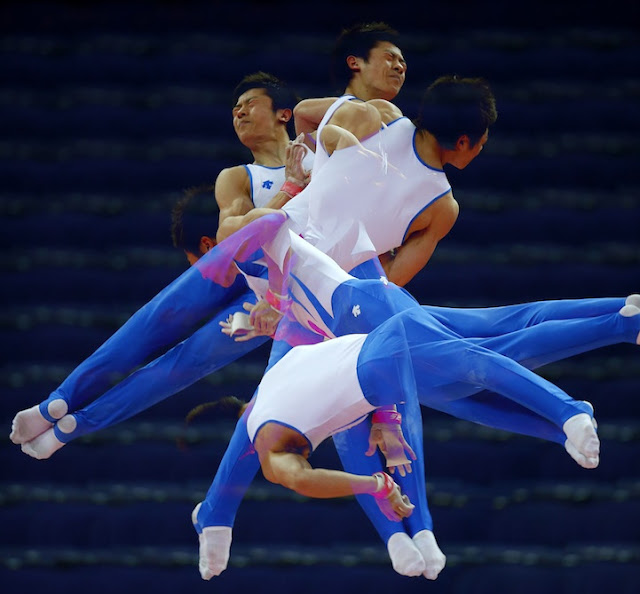 South Korea's Kim Soo-myun rotates above the horizontal bar during men's gymnastics podium training before the 2012 London Olympic Games in London July 25, 2012. Picture taken with multiple exposures.  REUTERS/Mike Blake  (BRITAIN - Tags: SPORT OLYMPICS GYMNASTICS) ORG XMIT: MB06