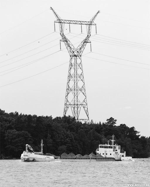 Lastbåt passerar genom Skeppsbackasundet. Hög mast med elledningar ovanför båten.