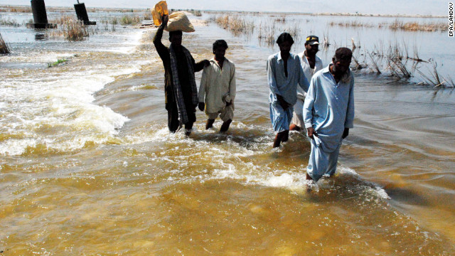 Residents of Sindh province in Pakistan walk through floodwaters, 1 October 2012. pardaphash.com