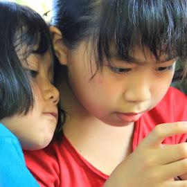 enjoying new gadget by Mozes Dama - Babies & Children Children Candids