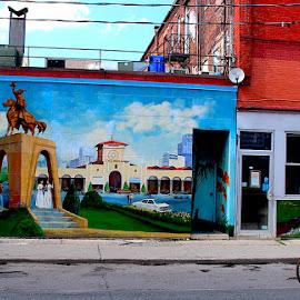 Biking by the Scenery by Ronnie Caplan - City,  Street & Park  Street Scenes ( painted, buildings, windows, scenery, street scene, bicyclist )