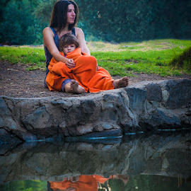At the river bank by Tzvika Stein - People Street & Candids ( water, child, orange, reflection, blanket, mother, green, woman, bank, morning, river )