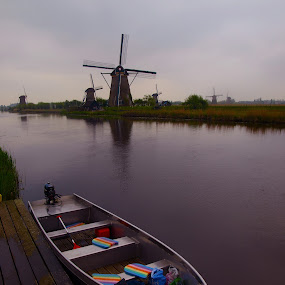 Kinderdijk by Ron Jnr - Landscapes Waterscapes ( nertherlands, kinderdijk, unesca, dutch, cloudy, overcast, boat, windmills, world heritage site, riverbank, river )