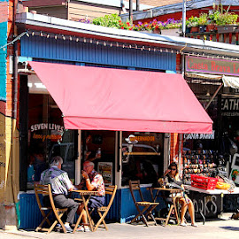 Seven Lives by Ronnie Caplan - City,  Street & Park  Neighborhoods ( streetscene, patio, cafe, restaurant, awning, people, sidewalk )