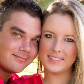 Young love by Wendy Van Zyl - People Couples ( beautiful light, just met and in love, blond, trees, bleu eyes, young couple, red shirts, smiling, river )