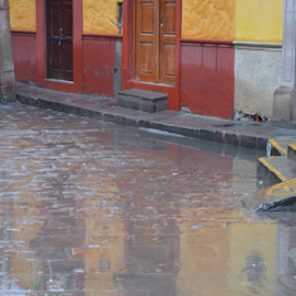 Reflections on a wet day  by Brian  Boyle - City,  Street & Park  Street Scenes ( reflection, photograph, mexico, street, brian boyle, yellow, street scene, photography, cobbles, red, puddle, bb, rain )