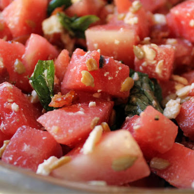 Summer Watermelon Salad With Crispy Bacon, Feta Cheese, Torn Basil, And Toasted Pumpkin Seeds
