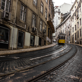 A curve by Julija Moroza Broberg - City,  Street & Park  Vistas ( curve, train tracks, pathway, street, old town, old city, yellow, lisbon, travel, old building, traffic, buildings, train, bricks, view, lisboa )