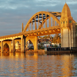 Bridge at Sunset by Lori Pagel - Buildings & Architecture Bridges & Suspended Structures ( calm, water, oregon, reflection, green, coastal, coast, mirror, florence, turquoise, blue, drawbridge, sunset, bridge, gold, wet, evening, golden, river )