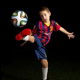 Low key portrait of a boy kicking a world cup football by Dotan Naveh - Sports & Fitness Soccer/Association football ( messi, #10, player, barca, cute, spain, kid, caucasian, child, argentina, ballgame, qatar airways, dark, young man, barcelona, athlete, soccer, ball, world cup, spanish, lionel, uniform, low key, grass, leo, sport, qatar, team, fun, game, stripes, fan, young, fc, 10, red, football, blue, lionel messi, israeli, footballer, night, proud, boy, athletic )