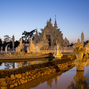 White Temple Sunset by Phil Hanna - Buildings & Architecture Places of Worship ( water, statue, sky, chiang rai, blue, sunset, white temple, thailand, reflections )