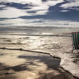 Waiting for the waves by Julija Moroza Broberg - Landscapes Beaches ( stormy, reflection, person, waterscape, shining, ocean, beach, atlantic, sihloutte, coast, old man, portugal, ocean view, water, sand, sihlouette, atlantic ocean, waiting, texture, sea, chair, pensioner, pattern, crutch, wave, symmetry )