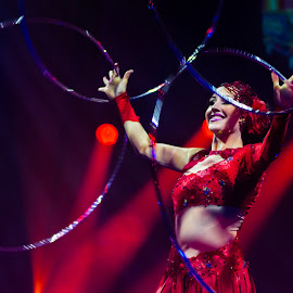 Hula hoop by Arti Fakts - People Musicians & Entertainers ( hula, hoola, show, hoop, circle, artifakts, stage, magic, juggler, red, woman, smile, light, entertainer, spotlight, circus )