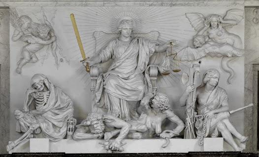 Boven de ingang van de Schepenzaal, onder Atlas, zit Justitia op haar troon. In haar handen houdt zij haar gouden zwaard der gerechtigheid en weegschaal. Achter haar straalt de zon van de goddelijke gerechtigheid.