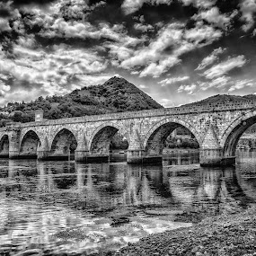 Bridge on Drina by Dobrinovphotography Dobrinov - Black & White Landscapes ( drina, old, famous place, mountain, europe, arch, ivo, stone, architecture, united nations educational, visegrad, bosnia and hercegovina, traditional culture, aging process, andric, style, restoring, travel locations, ottoman empire, social history, historic world event, journey, sunlight, landscaped, sokolovic, recovery, riverbank, architecture and buildings, history, serbia and montenegro, urban scene, building exterior, islam, serbia, cuprija, column, summer, scientific and cultural organization, bridge, day, built structure, waterfront, river,  )