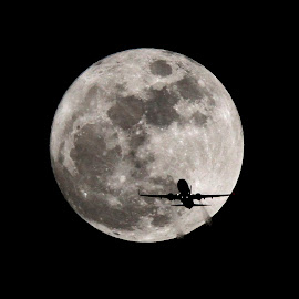 Wolf Moon and plane by Raul Roa - News & Events Science ( moon planes sky space astrophotography photojournalism photo )