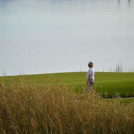 A nice walk by Thomas Shaw - People Portraits of Men ( water, golf course, walking, blue, bushes, grass, sun rise, green, lake, relaxing, man, shirt )