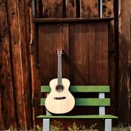 Guitar on a wooden bench by Denny Gruner - Artistic Objects Musical Instruments ( guitar grip, color image, hut, grass, green, guitar string, guitar, brown, guitar neck, garden )