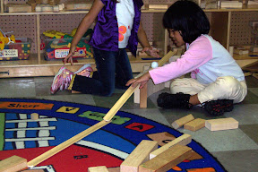 Children explore motion and force using ramps made of cove molding and marbles.