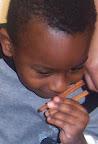 Child smells cinnamon sticks and smiles.