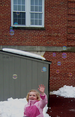Child reaching for floating soap bubbles.