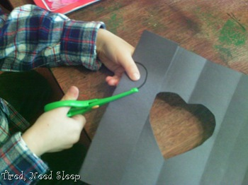 M cutting out hearts on folded lines