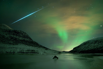 The Northern lights shimmer gently over the wintry coast of Tromsø Norway, contrasted with the streak of a meteor from the Geminid meteor shower