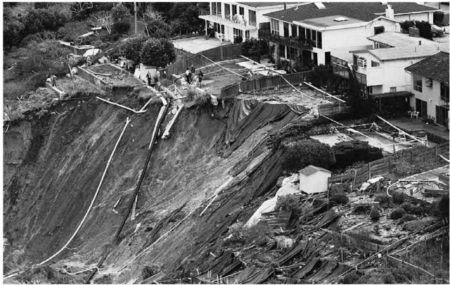 A MUDFLOW CAUSED BY HEAVY WINTER RAINS BRINGS DOWN THE HILLSIDE UNDER HOMES IN MILLBRAE, CALIFORNIA.