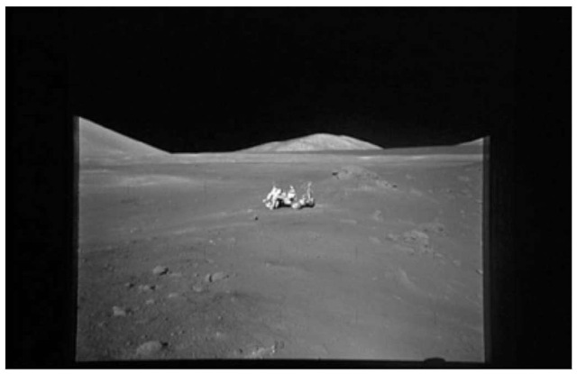 View of the Station 4 area, the site of the orange volcanic glass on the southern rim of the 110-m diameter Shorty Crater (to the right). The orange glass deposit lies just this side of the large boulder on the rim of Shorty, behind and to the right of the lunar roving vehicle and the author (courtesy of NASA). This figure is available in full color at http://www.mrw.interscience.wiley.com/esst.
