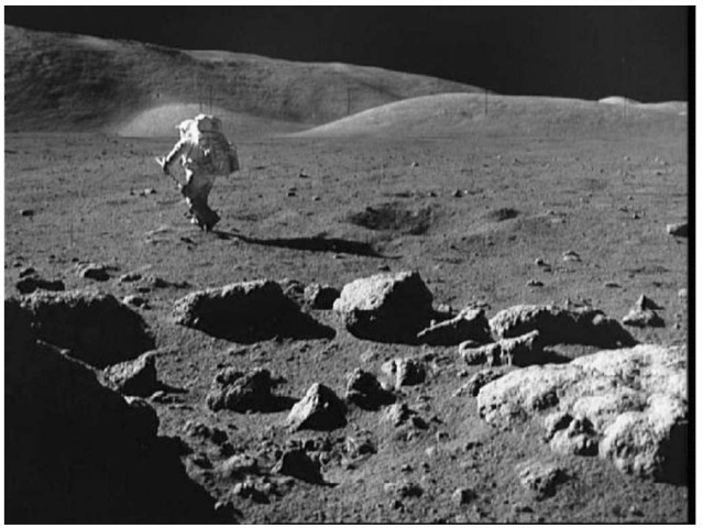 Mare basalt boulders at Station 5 on the rim of Camelot Crater excavated from a depth of about 150 m. The author is moving toward the Lunar Rover.This figure is available in full color at http://www.mrw.interscience.wiley.com/esst.