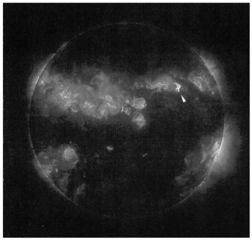 "A high-resolution X-ray image of the solar corona that has active regions and a flare (indicated by the arrow). The angular resolution is 0.75"", and the temperature of the brightest areas is about 3 x 106 K. This image was made by L. Golub et al. in 1989 from a rocket using the 0.25-m X-ray telescope NIXT (Normal Incidence X-ray Telescope) in a narrow wavelength range around 6.35 nm; this range includes the emission lines of Fe XVI at 6.37/6.29 nm and of Mg X at 6.33/6.32 nm. In contrast to an image-forming X-ray telescope of the Wolter type that has grazing incidence, here the image is produced at normal incidence as by an orinary optical mirror. Reflection of the X rays is made possible by vapor deposition of alternating thin layers of cobalt and carbon, so that constructive interference results for the wavelength 6.35 nm. NIXT was developed by L. Golub and co-workers at the Smithsonian Astrophysical Observatory. Cambridge, together with the IBM Thomas J. Watson Research Center, Yorktown Heights, New York (photo courtesy of SAO and IBM Corp.). (See Reference 46 for description of rocket flight.) This figure is available in full color at http://www.mrw.interscience.wiley.com/esst."