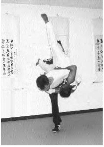 When fighting, baguazhang practitioners twist and weave about their opponents, emphasizing the use of the open hand in preference to the closed fist. Two men demonstrate a throw using this distinctive technique at the Shen Wu Academy of Martial Arts in Garden Grove, California.