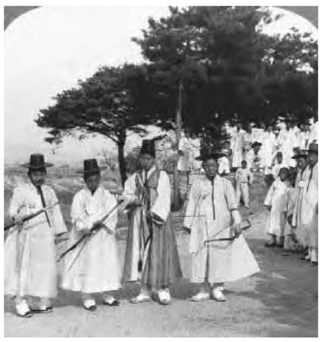 Winners of an archery contest in Korea stand together in the winners' circle, ca. 1900.