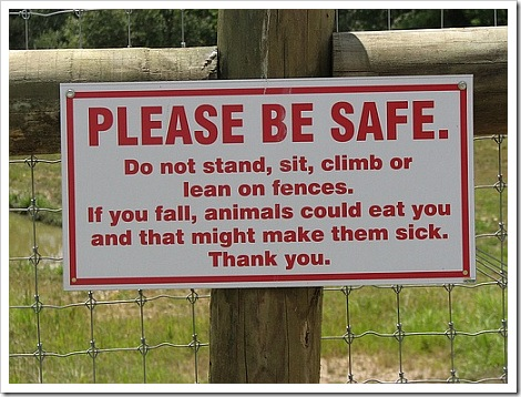 Funny sign picture | Please be safe. Do not stand, sit, climb or lean on fences. If you fall, animals could eat you and that might make them sick. Thank you.